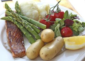 Stekt lax med grön sparris, färsk potatis och grönsaker är mat som vi längtar efter just nu. Foto: Dan Strandqvist