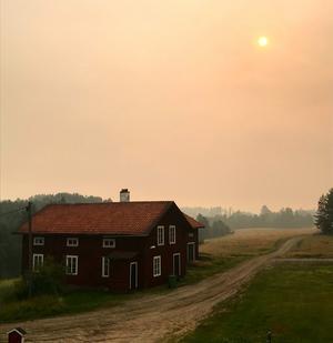Bilden är tagen under dagen då det var blå himmel och sol. Brandröken har legat så tjockt över byn att det har sett ut som ständig kvällssol.