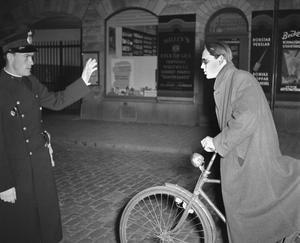 Polis stoppar cyklisten Göran Gårder på Köpmangatan i oktober 1947. Fotograf:Specialfoto (Åke Ahlstrand, Börje Gustavsson, Jan Holmlund och Rolf Carlsson).