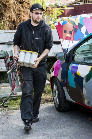 Thomas Öberg laddar upp bilens batteri med ett extra batteri för att kunna spela burpen.