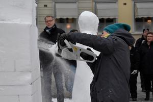 Med motorsågen tar Lena ut den yttre formen av sin snöskultur innan hon börjar mejsla fram alla fina drag.