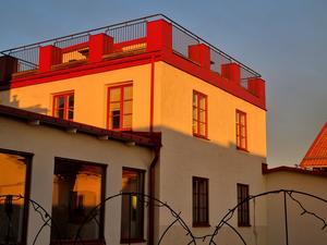 Det är blå himmel och morgonsolen speglar sig fint i fönstren och på husfasaden den 2 mars.Foto: Inga-Lill Isberg.