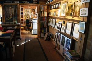 En av väggarna i ateljén visar en del av Lars Mortimers rika produktion. Längre in skymtar hans arbetsrum där han tecknade sina serier.