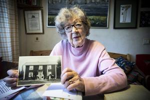 Stina Eliasson visar upp en bild på huset som är tagen vid sekelskiftet. På bilden är Stinas pappa bland andra.