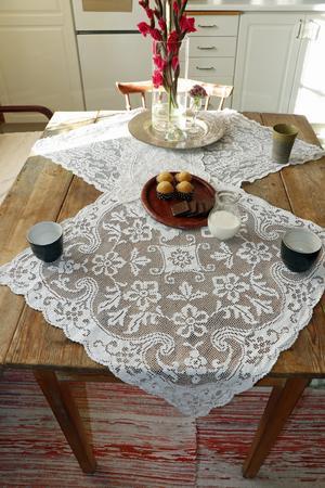 Liselotte tycker om att möbler har en sliten yta, att det syns att de använts. Spetsdukarna kontrasterar snyggt.