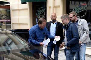 Stefan Löfven delar ut biljetter inför matchen.
