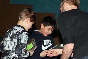 Hugo och Ardar belönades med varsin bok för sina insatser under bibliotekets tipspromenad.