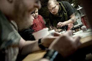 Nybörjare. Peter Hakulinen visar bröderna Simon och Erik Grundelus hur man ska måla spelfigurerna.