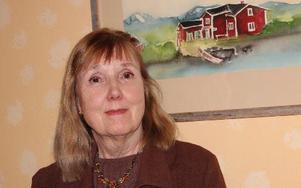 Margareta Sarri vid tavlan i köket som föreställer hennes mormors barndomshem vid Kalixälven i Norrbotten. Den är målad av Elis Aidamnpää. – Jag har skrivit en bok om min mormors pappa som hade ett otroligt intressant livsöde, säger hon.