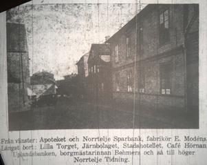 Från vänster: Apoteket och Norrtelje Sparbank, fabrikör E Modéns. Längst bort: Lilla Torget, Järnbolaget, Stadshotellet, Cafe Hörnan, Uplandsbanken, borgmästarinnan Behmers och så till öger, Norrtelje Tidning.
