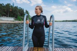 Genom att använda våtdräkt kan Catarina Malmström simma i Mälaren istället för i simhallen under hela sommarhalvåret.– För mig ger simningen utomhus mycket mer än att simma i en bassäng. Jag älskar att stoppa huvudet under vattenytan och vara ett med vattnet, säger Catarina Malmström. Bild: Ola Jacobsen
