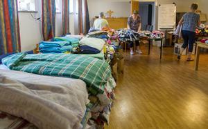 Bord fyllda med lakan, handdukar, stickade mössor och kläder som ska packas ihop. Ett 20-tal hjälptes åt att packa ned kläderna som ska transporteras ned till Vitryssland.