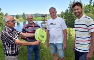 Rolf Pellas, till vänster, gav en hjärtstartare till badet och bystugan i Västannor-Smedby – representerad av förningens ordförande Sven-Åke Petters – och tackade Nils Berglund, tvåa från höger, och Magnus Knuts, längst till höger, för att de räddat hans liv.