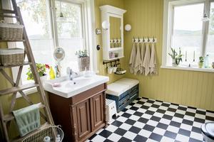 Badrummet har renoverats med smarta återbrukslösningar. En gammal möbel blev ett personligt badrumsskåp under tvättstället.