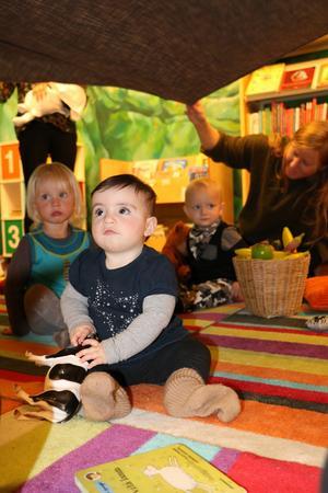 Sju månader gamla Eugenia tittar fascinerat på alla mammor som skakar ett tygstycke över hennes huvud.