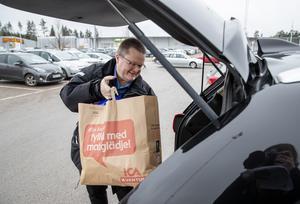 Ulf Larsson lastar in matkassarna med de sista färskvarorna till jul i bilen.