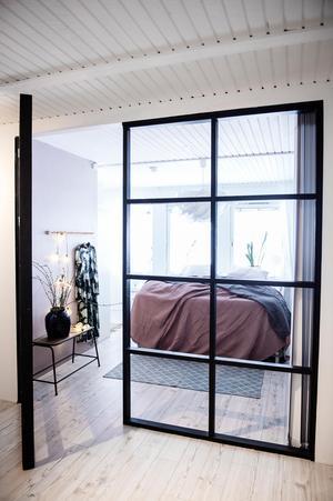 Rumsavdelaren är byggd i trä och  är en fönstervägg, utan glas.