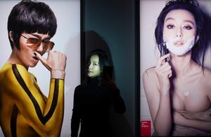 Den kinesiska fotografen Chen Man mellan sina porträtt av skådespelerskan Fan Bingbing. Foto: Hossein Salmanzadeh / TT