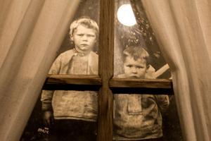 Ute på logen tittar den lille Dan Andersson, till höger i bild, upp på fotografen. Bilden hänger i utställningslogen på Rikkenstorp.
