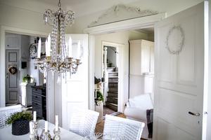 Matsalen är ljus och över pardörren som leder till vardagsrummet  har Ann-Katrin satt upp ett dekorativt överstycke från ett gammalt skåp.