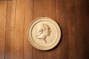 Porträttmedaljong gjord av Sergel-eleven Erik Gustaf Göthe som föreställer historiemålaren Gustav Cederströms farfar. Även väggarna i hallen har Jan stänkmålat.