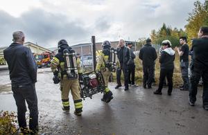 Brandmännen bär in fläktar för att få ur all rök ur lokalerna. Båda delägarna står upptagna i telefon. Ingen får inte vara på området  under släckningsarbetet.