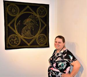 Gisela Nilsson med sin drake. Tekniken är heltyg, kviltad i ett stycke. Draken omgärdas av de fyra symbolerna för eld, luft, vatten och jord.