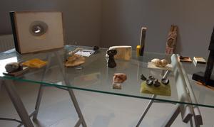Ett bord med blandade småsaker, som kanske är ett konstverk tillsammans, eller många konstverk.