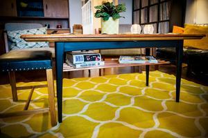 Vardagsrumsbordet  kan vecklas ut och bli ett matbord. Joakim har svärtat underredet och byggt till en tidningshylla i kopparrör.