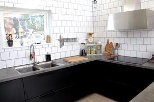 Svart köksinredning utan överskåp och bänkskivor av betong som hon har tillverkat själv.