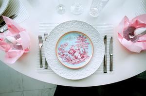 Dubbla tallrikar där den lilla tar upp ett känt textilmönster. Rosa servetter tar upp färgen.