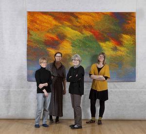 Ebba Bergström, väverska, Frida Lindberg, ägare till Alice Lund Textilier, Helena Hernmarck, konstnär, och Tove Wibrant väverska, framför vävnaden Passing Fall. Såväl Helena som Alice Lund Textilverkstad deltar i sommarens stora utställning i OA-museet.