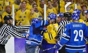 Finlands Rasmus Ristolainen slår Sveriges Robert Hägg i ishockeymatchen mellan Sverige och Finland i junior-VM, grupp B, på Malmö Arena på lördagen.