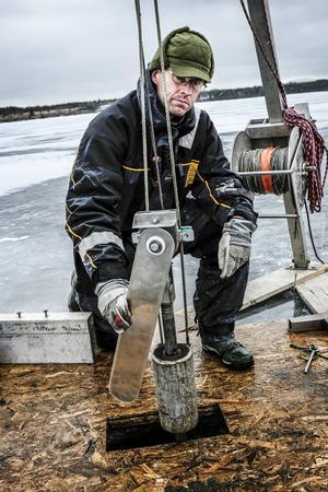 Dan Hammarlund, professor i kvartärgeologi vid Lunds universitet, sänker ner borrkärnan för att ta sedimentprover.
