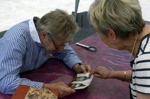Ingegerd Mellberg visar Jörgen Martinsson foton på sitt gamla hörnskåp i trä.
