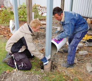 Helst ska plintarna gjutas så djupt att de hamnar under  tjälen. Peter Sellén och Torbjörn Lundström hjälps åt med arbetet.