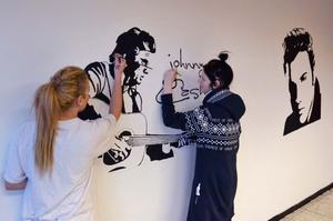 Linn Särnblad och Emma Viborg målar ett porträtt av Johnny Cash. På varsin sida sitter även porträtt av Elvis och Marilyn Monroe.