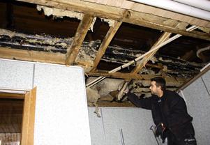 Snickaren Magnus Waltersson river ur isolering från taket på damernas omklädningsrum vid Djupadalsbadet. Rören har spruckit så att vattnet har sprutat åt alla håll. BILD: SAMUEL BORG