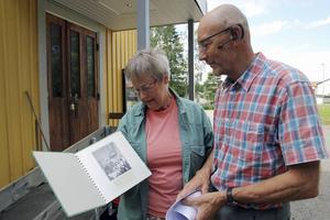 Elvi Sandberg och Sven Bergström tittar på gamla bilder av missionshuset i Backa, som nu är klubbhus för Forsa OK.