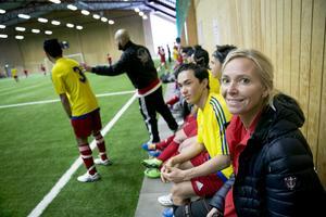 Marie Åberg Persson njuter av matchen från Gemenskapslagets avbytarbänk