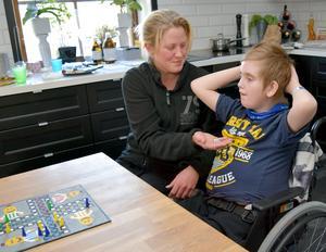 Pernilla Berglund försöker få sonen Hampus att för en stund glömma smärtorna i fötterna och magen.