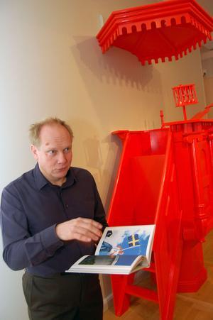 Utställningen i Zornmuseets andra plan och boken till utställningen går hand i hand, poängterar Peter Johansson, som här bläddrar i boken i det inredda rödfärgade kyrkorummet.