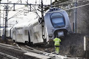 Första enheten i tågsättet körde upp på jordvallen vid spårets slut och knäckte en kontaktledningsstolpe. Personal från Trafikverkets entreprenör överblickar skadorna.