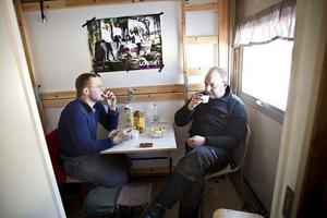 Joakim Dübbel och Fredrik Andersson har lunchrast. Maten har de värmt i mikron.