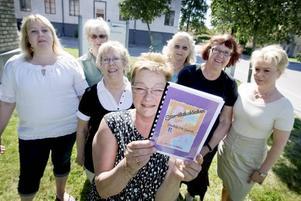 Inger Olsson Åström håller upp Storvikskokboken där ortsbor har bidragit med sina favoritrecept. Camilla Hedberg, Maritta Fridolfsson, Barbro Andersson, Heidi Heimerlöv, Harriet Österbom och Lena Nordkvist är också engagerade i projektet.