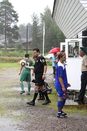 Domare Mats Tjernberg tillsammans med lagkapperna Henrik Paulsson, Ilsbo, och Albin Isaksson, Bollnäs när matchen sattes igång igen efter regnet.