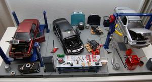 En glasmonter fylls av en komplett liten verkstad i modellformat där varje detalj från stora bilar ned till minsta lilla verktyg finns med.
