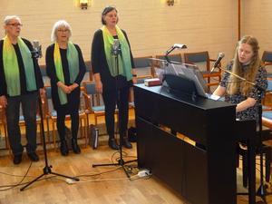 Gullänget kyrkokörs lilla skara, från vänster Ingrid Olofsson, Gunilla Ekenberg och Maj Inger Forsberg i vackra sjalar samt körledaren Lina Sundqvist vid pianot.