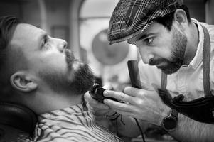 Omad är har full fokus och är stadig på handen när han trimmar skägget på Tobias Anderssson.