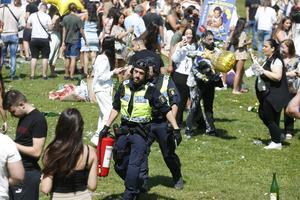 Polis bär bort brandsläckare under det tumultartade studentfirandet i Dalparken i förra veckan.